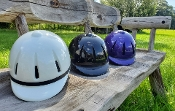 three helmets on rustic bench. White-Black-purple. Highly reflective polymer shell.